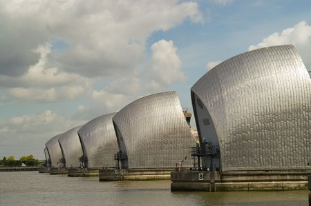 famous industries: Detail of Thames Barrier on river Thames, against blue sky with clouds
