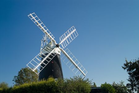 Stretham windmill against clear blue sky with green trees in foreground photo