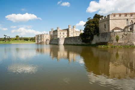 mote: Castle and reflection on lake or mote against blue sky with clouds Stock Photo