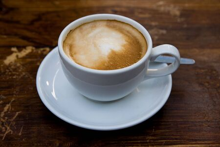 Close up of a cup of caffe latte coffee on a wooden table