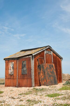 Abandoned old rusty shed with a gravel foreground against blue sky photo
