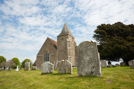 Old St. Clements church and graveyard against blue sky with white clouds, Old Romney, Kent, UK