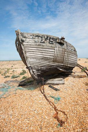 barca da pesca: Abbandonato il naufragio della barca da pesca in legno sulla spiaggia contro il cielo blu