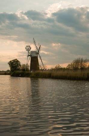 Windmill by a river, with reflection at sunset, How Hill, Norfolk, UK