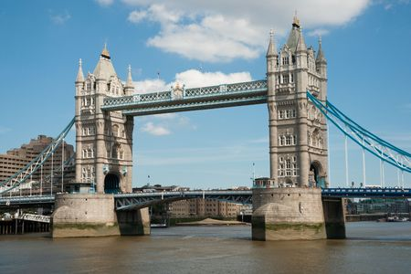 Tower Bridge over the Thames, London, against blue sky with white clouds
