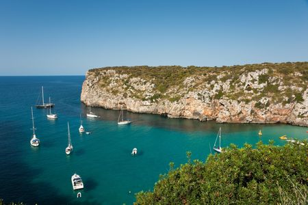 en: Landscape of Cala En Porter, Menorca, detailing the cliffs and several boats