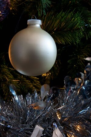 Detail of beige bauble and silver tensil on a christmas tree Stock Photo
