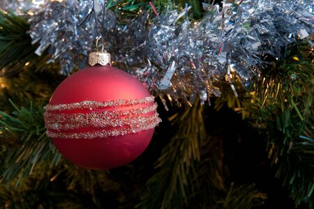 Detail of red bauble and silver tensil on a christmas tree