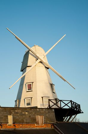 Traditional white wood windmill at sunset against clear blue sky in Rye, East Sussex, UK