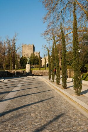 Road lined with several tress leading into medieval castle in Guimaraes, Portugal Stock Photo