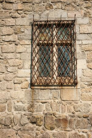 Old window with rusty metal frame in a stone wall