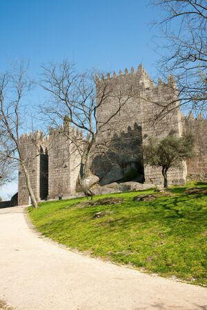 Old medieval stone castle in Guimaras, Portugal, with park and against blue sky