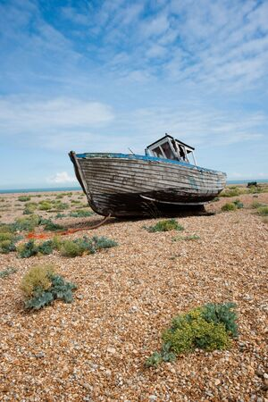 Old abandoned shipwreck on gravel shore with some plants against a blue sky with some white clouds