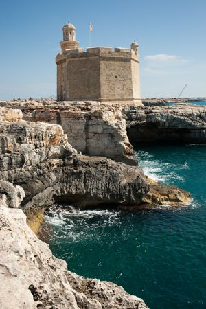 Old tower fortress on rocks by the sea against blue sky, Ciutadella de Menorca, Menorca, Spain