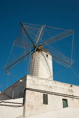 Traditional white windmill in Menorca, Spain, against blear blue sky