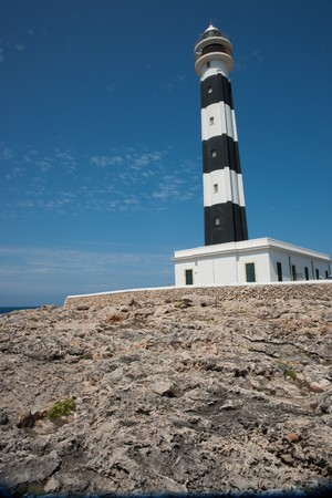 Detail of black and white lighthouse at  Cap dArtruitx, Menorca, with rock in the foreground and against clear blue sky