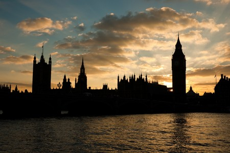 Houses of parliament and Big Ben in silhouette at sunset with moody sky