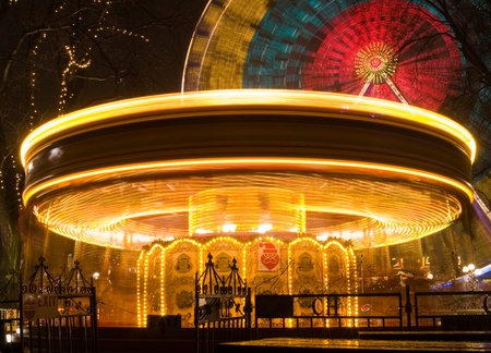 Merry go round lit up at night with Ferris wheel in background