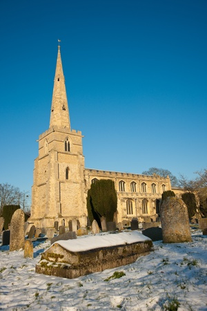 cambridgeshire: St Andrews Church and graveyard covered in snow against clear blue sky, Cambridge, UK