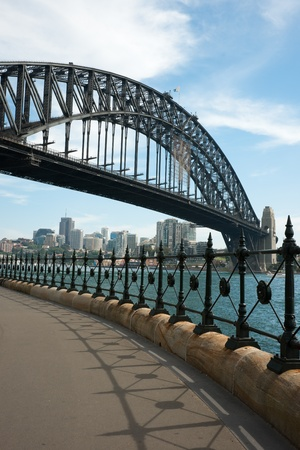 Sydney, Australia - 18 February 2011 : Sydney Harbour Bridge and metal fence against blue sky with some white clouds Stock Photo