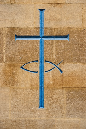 Blue cross and fish carved into stone, a symbol of christianity Stock Photo