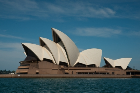 Sydney, Australia - 19 February 2011 : Side view of the Sydney Opera House from the harbour, against a blue sky with some white clouds Editorial