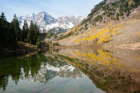 Maroon Bells mountains, with lake and reflection and green pines and yellow aspens, Aspen, Colorado, USA