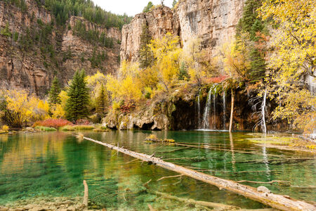 Hanging Lake, amidst autum colours with red, yellow and green plants Stock Photo