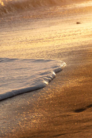 wave breaking on the sand of the beach forming white foam