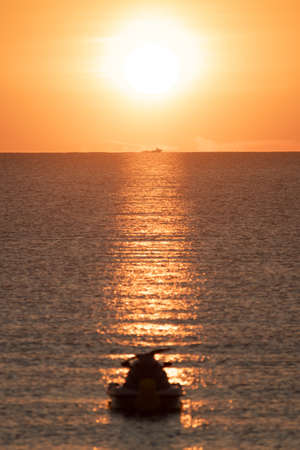 Sunrise with jet ski in the foreground and fishing boat in the background sailing in front of the sun