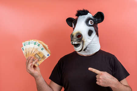 boy with funny latex cow mask holding money with one hand and pointing to it with the finger of the other hand and pink background
