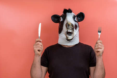 person disguised as a cow showing a knife and fork on a pink background
