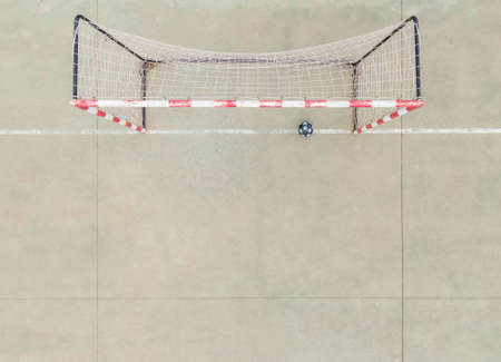 top view of a 7-a-side soccer goal with its net and a black ball with stars