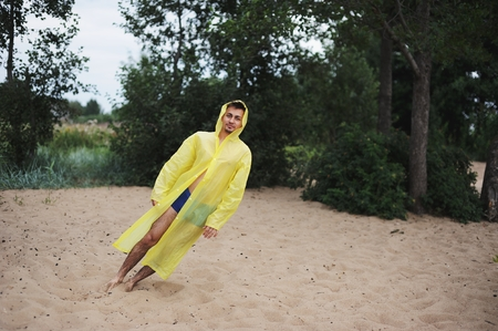 blown away: man in yellow raincoat blown away by the wind falls