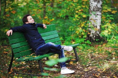 Attractive dark-haired man in jacket and jeans sits on a bench near the birches in autumn Park alone, imposingly lounging and resting his foot on the leg, smiles