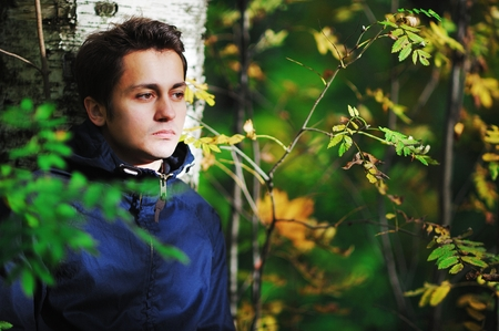 Young brown-eyed man with a sad face leaned against the birch tree and sad looking to the side in autumn forest in Sunny day.