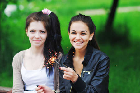 igniting: Portrait of a happy young women with long dark hair. Two beautiful girlfriend was found in the summer on holiday and having fun, igniting sparklers.