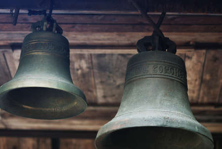 wooden  ceiling: two bronze bells under the wooden ceiling Stock Photo
