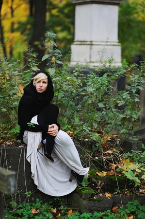 Solitary woman mourning and sitting on gravestone, remembering dead relatives in on cemetery.