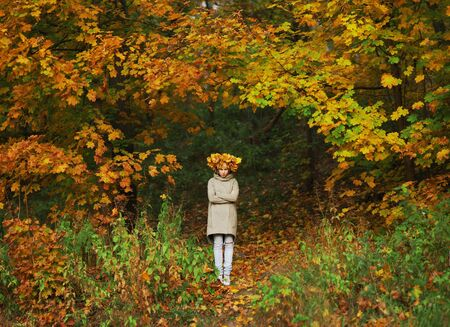 sombre: Young frowning girl with a wreath of autumn maple leaves on the head is on the forest path between trees Stock Photo