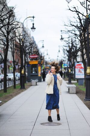 wind down: Beautiful happy woman enjoying the walk and goes down the avenue, the wind ruffled her hair Stock Photo
