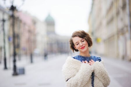 embarrassment: Beautiful young smiling girl posing on the boulevard in the center of St. Petersburg, closing her eyes in embarrassment. Stock Photo