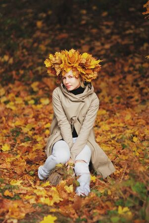 inscrutable: Young beautiful smiling girl with a crown of autumn maple leaves sitting on fallen leaves in the forest.