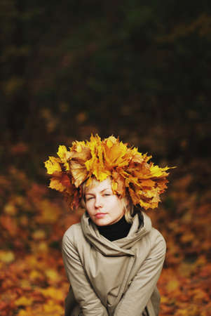 inscrutable: beautiful young girl in autumn park with wreath of leaves, close-up.