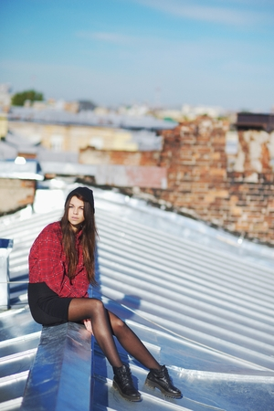 svelte: Portrait of thoughtful courageous young girl sitting on the visor iron roof of high-rise buildings.