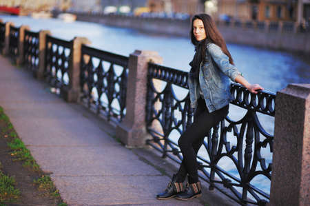 parapet: beautiful girl in blue jeans jacket and scarf straightens hair standing near the parapet on the embankment. In her hand brown elegant handbag