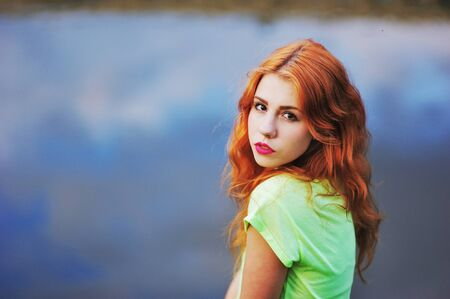 Portrait of a very beautiful brown eyed girls with bright red hair in a light green dress on a background of lake