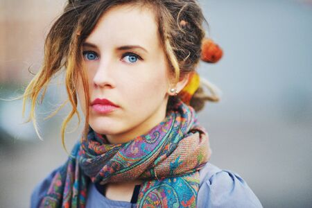 Gorgeous portrait of a young serious girl with beautiful blue eyes and youthful hair in the scarf with a color picture, closeup. Stock fotó