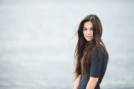 Portrait of beautiful brown-eyed girl with long, tangled from the wind, hair in a dark shirt on grey-blue background