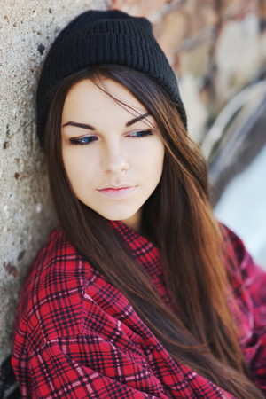 downcast: Young beautiful long-haired brunette girl in a black hat with downcast eyes at a brick wall, close-up. Stock Photo